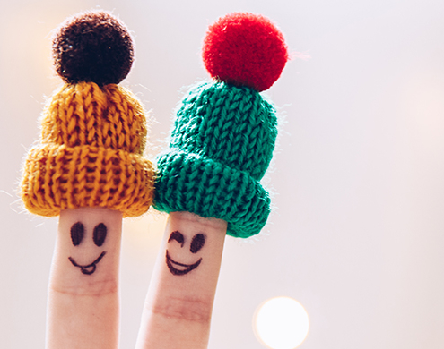 Reducing Stress Funny couple fingers on knitted winter warm hats smiling and wink